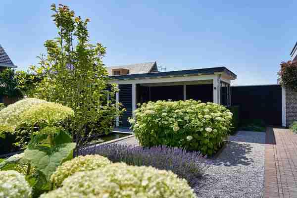 een zwart tuinhuisje in een moderne tuin