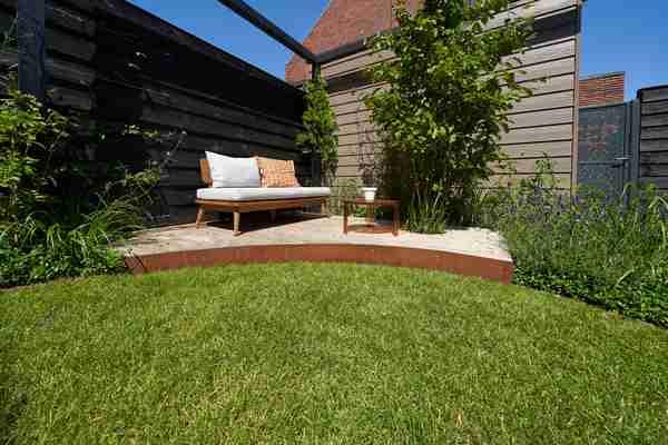 een strak terras in de hoek van een groene tuin